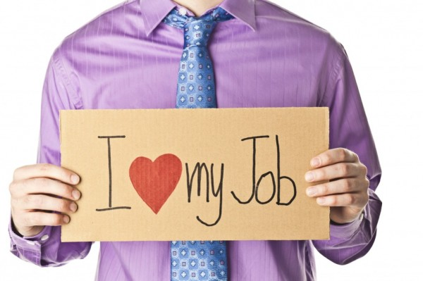 man holding a i love my job sign