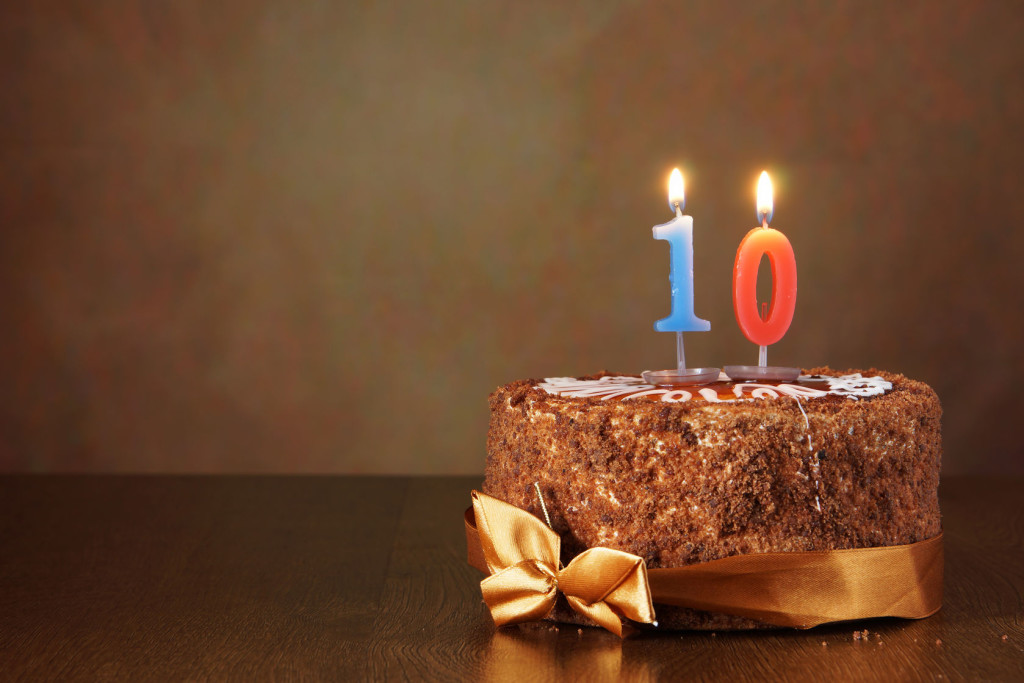 Birthday chocolate cake with burning candle as a number ten on brown background
