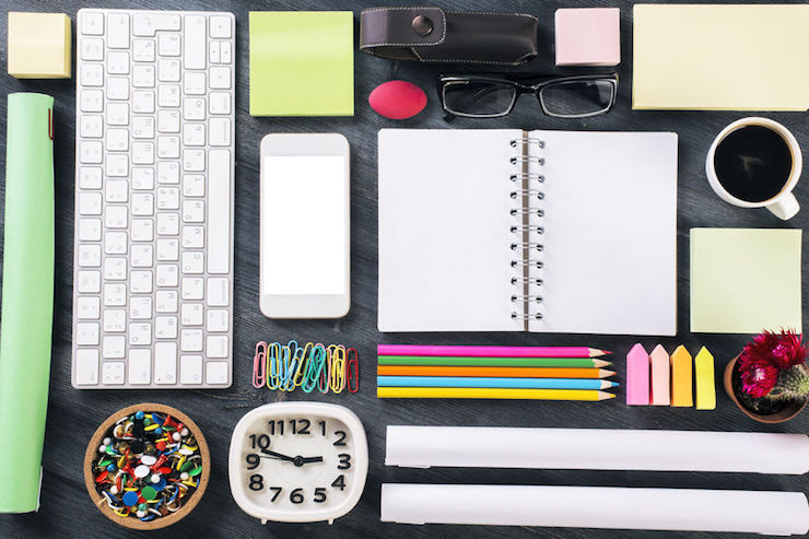 top view of wooden office table with blank white smartphone, keyboard, clock, notepad, coffee cup and other items organized in a neat and creative manner