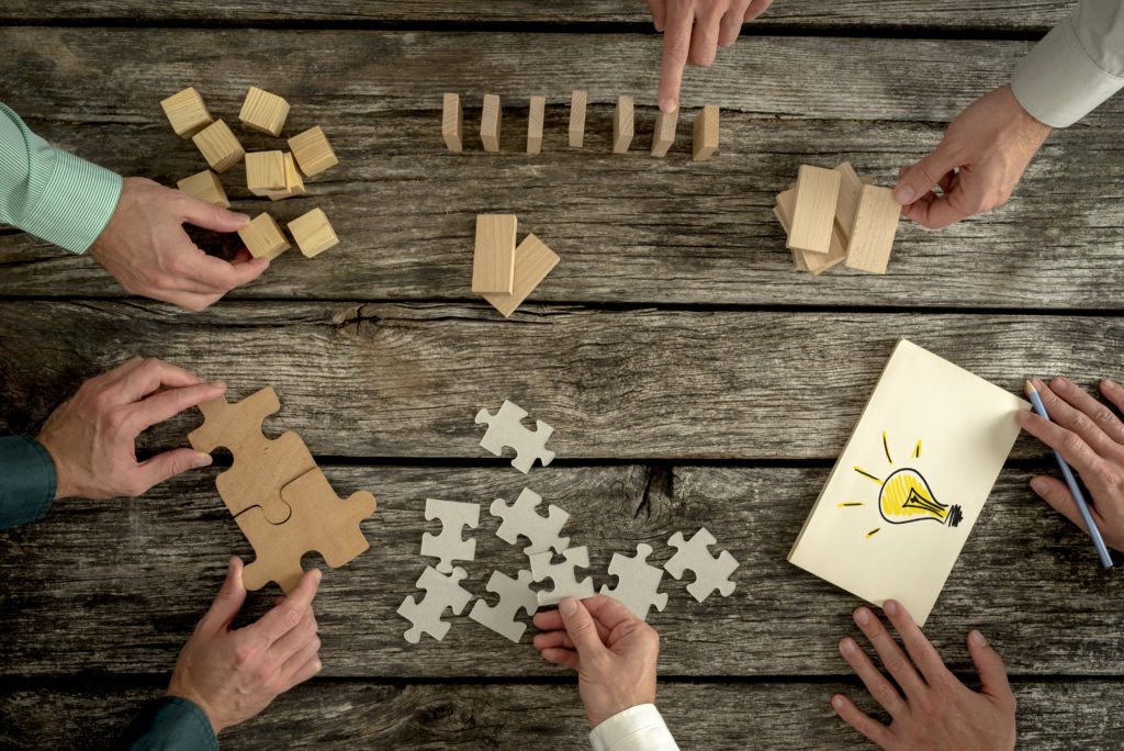 Business men using puzzle pieces to demonstrate teamwork