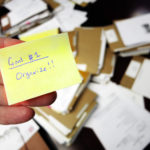 Messy office with hand holding note saying Get Organized